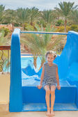 Little girl near water park slides — Stock Photo