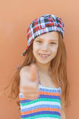 Smiling girl in dress raises thumbs-up — Stock Photo