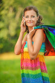 Woman in colorful dress of said cellular phone — Stock Photo