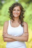 Portrait young curly hair woman arms crossed smiling — Stock Photo