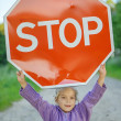 "Little girl holding a red sign ""STOP"" — Stock Photo"