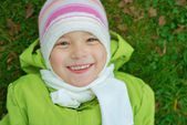 Smiling little girl in green jacket — Stock Photo