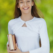 Smiling teenage girl with red book — Stock Photo #37401017