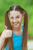 Smiling teenage girl picks up big thumbs up — Stock Photo