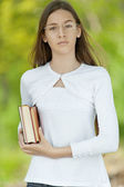 Teenage girl dressed in white with books — Stock Photo