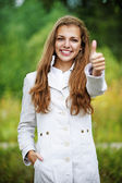 Smiling beautiful woman lifts thumbs upwards, — Stock Photo