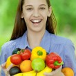 Teenage girl holding banana, peppers, pears and oranges — Stock Photo