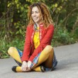 Stock Photo: Womwith dreadlocks sitting in lotus position