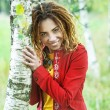 Stock Photo: Womwith dreadlocks near birch