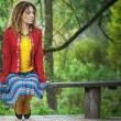 Womwith dreadlocks sitting on bench — Stock Photo #39993847