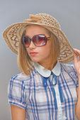 Jonge vrouw in zonnebril en stro hoed — Stockfoto
