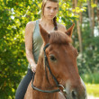 Beautiful young woman on horseback — Stock Photo #40292493