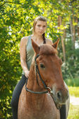 Beautiful young woman on horseback — Stock Photo