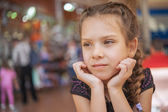 Sad little girl in market — Stock Photo