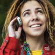 Womwith dreadlocks talking on phone — Stock Photo #40489769