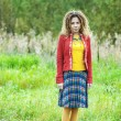 Foto de Stock  : Womwith dreadlocks standing k on grass