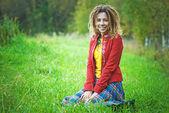 Vrouw met dreadlocks zittend op het gras — Stockfoto
