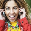 Stock Photo: Smiling womtalking on two mobile phone