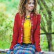 Stock Photo: Womwith dreadlocks sitting on bench