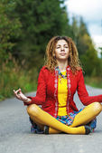 Woman with dreadlocks sitting in lotus position — Stock Photo