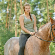 Stock Photo: Young beautiful womrides horse