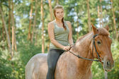 Young beautiful woman rides horse — Stock Photo