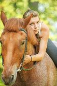 Beautiful young woman on horseback — Stock Photo