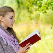 Beautiful woman reading red book — Stock Photo