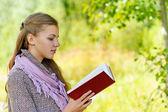 Beautiful woman reading red book — Stock Photo