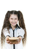 Little girl holding bowl with sesame — Stock Photo