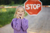 """Little girl about red sign """"STOP"""" — 图库照片"""