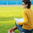 Girl reads book on lawn — Stock Photo