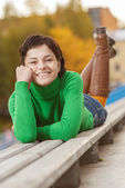 Pretty young woman lying on bench — Stock Photo