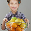 Little girl holding a basket of apples and oranges — Stock Photo #45620257