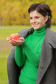 Smiling cute woman bites ripe apple — Stock Photo
