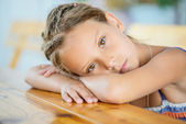 Little girl sitting at table — Stock Photo