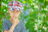 Little girl puts index finger to lips — Stock Photo