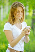 Fair-haired woman looking at phone — Stock Photo