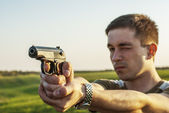 Young man took aim with pistol — Stock Photo