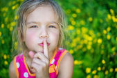 Cheerful girl puts index finger to lips — Stock Photo
