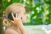 Little girl talking on cell phone — Stock Photo