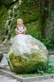 Little girl sits on large stone — Stock Photo
