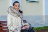 Woman in white coat sitting on bench — Stok fotoğraf