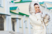 Smiling beautiful woman in white coat — Stock Photo