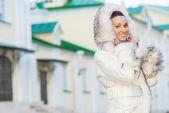 Smiling beautiful woman in white coat — Stock Photo
