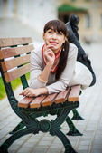 Beautiful girl lays on bench — Stock Photo