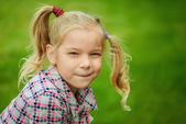 Portrait of little pretty girl playing at summer green park — Stock Photo
