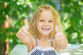 Cheerful girl lifts thumb upwards — Stock Photo