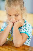 Sad little girl sitting at table — Stock Photo