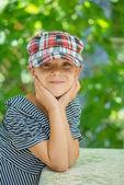 Little girl talking in plaid cap — Stock Photo
